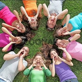 group of kids or teens shouting or singing at summer camp
