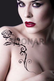 Sensual beautiful nude brunette girl with tribal tattoo rose