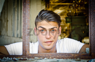 Handsome young man with funny expression in rusty window