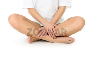 slender naked legs being massaged isolated on white