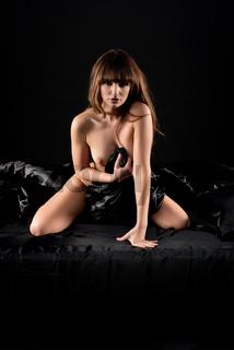 Nackte junge Frau im Bett mit schwarzer Seide