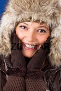 Junge Frau mit Pelzmütze und Handschuhen lacht