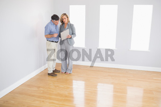 Serious blonde realtor showing a room and some documents to a potential buyer