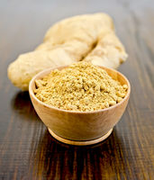 Ginger powder in a bowl with the root