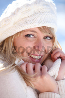 Woman snuggling up to her warm clothes