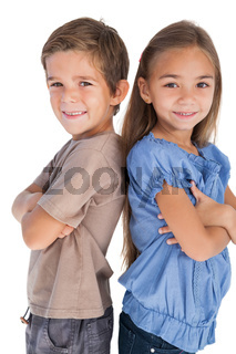 Children standing back to back with their arms crossed