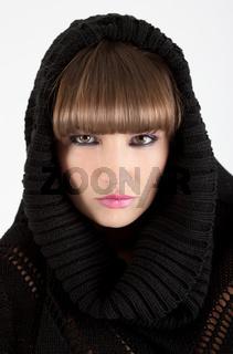 Schoene junge Frau mit schwarzem Strick-Pullover vor weiss.