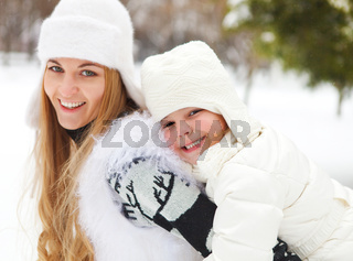 Young blond mother with daughter having fun outdoors