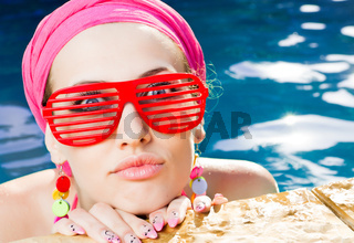 beautiful woman with red sunglasses in the pool
