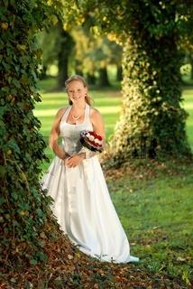 Beautiful bride portrait with flower in park