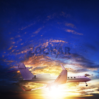 Small private jet in sunset sky. Square composition.