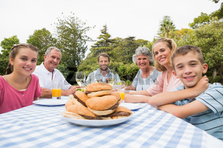 Extended family eating outdoors at picnic table