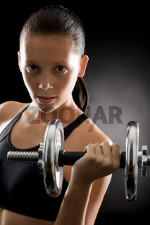 Active woman exercise weights on black background