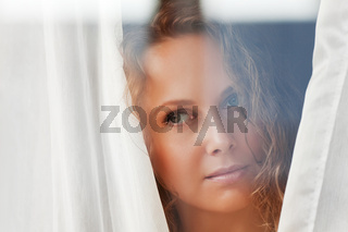 Beautiful woman looking through a window