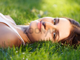 Beautiful young girl relaxing on green grass