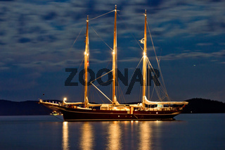 Wooden sailboat illuminated at night