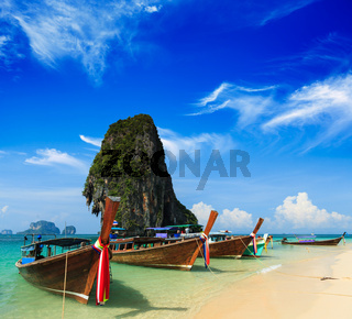 Long tail boat on tropical beach with limestone rock