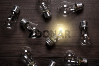 glowing bulb over wooden background uniqueness concept