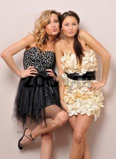 Two beautiful women in fancy dresses.
