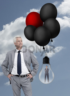 Businessman standing next to businesswoman inside light bulb held by balloons