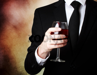 Young man holding a glass of red wine