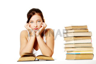 Young girl holding her head and sitting with books.