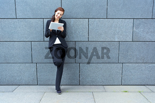 Geschäftsfrau mit Tablet Computer an Mauer