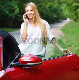Young woman standing near a  sports car and talking by mobile phone