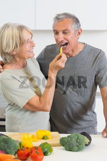 Husband tasting a slice of yellow pepper