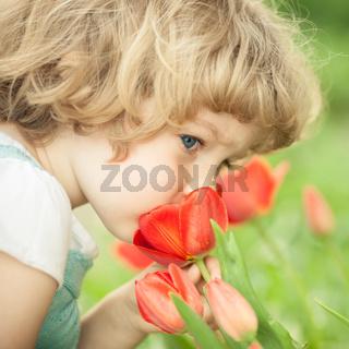 Child smelling tulip
