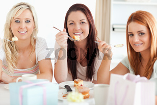 Charming Women sitting at a table eating a cake