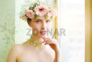 beautiful girl wearing wreath of flowers on light background
