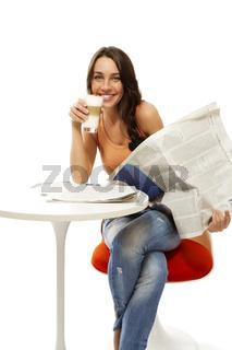 glückliche junge frau mit einer zeitung und einem glas latte macchiato kaffee