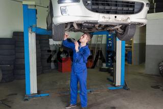 Repairman working under raised car