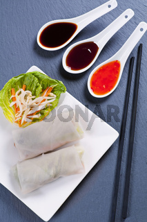 Spring rolls with sauces on black background