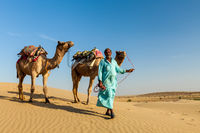 Rajasthan travel background - Indian cameleer (camel driver) with camels in dunes of Thar desert. Jaisalmer