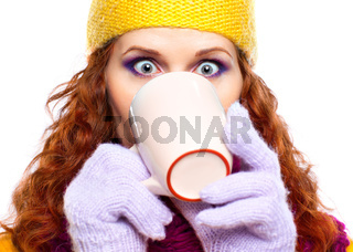 Beautiful girl wearing winter clothes with cup