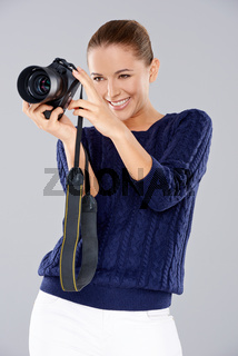 Happy woman holding a professional camera