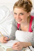 Smiling girl preparing for exams in bed