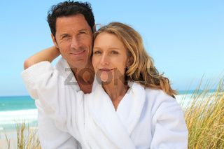 Couple relaxing on the beach in toweling robes