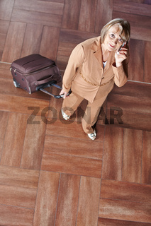 Seniorin zieht Rollkoffer und telefoniert