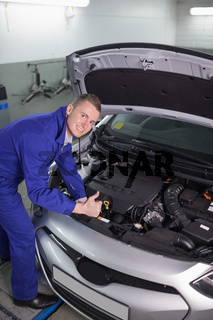 Mechanic leaning on a car while looking at camera