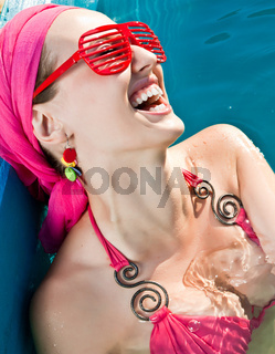 beautiful smiling woman with red sunglasses in the pool