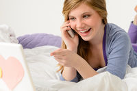 Laughing teenager relaxing by speaking on phone