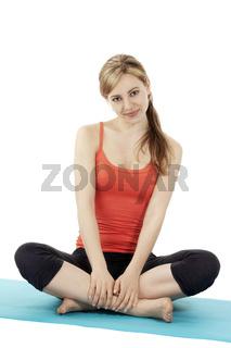 hübsche sportlerin sitzt auf ihrer fitness matte