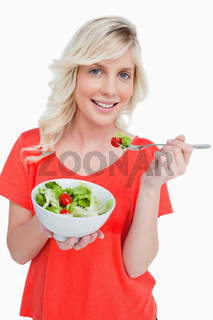 Young smiling woman eating a fresh salad with a fork
