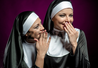 Young attractive nun whispering a secret to another nun