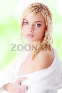 Young woman dressed in white bathrobe