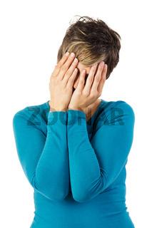 Junge Frau hält ihre Hände vor das Gesicht