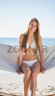 Beautiful blonde sitting on hammock and smiling